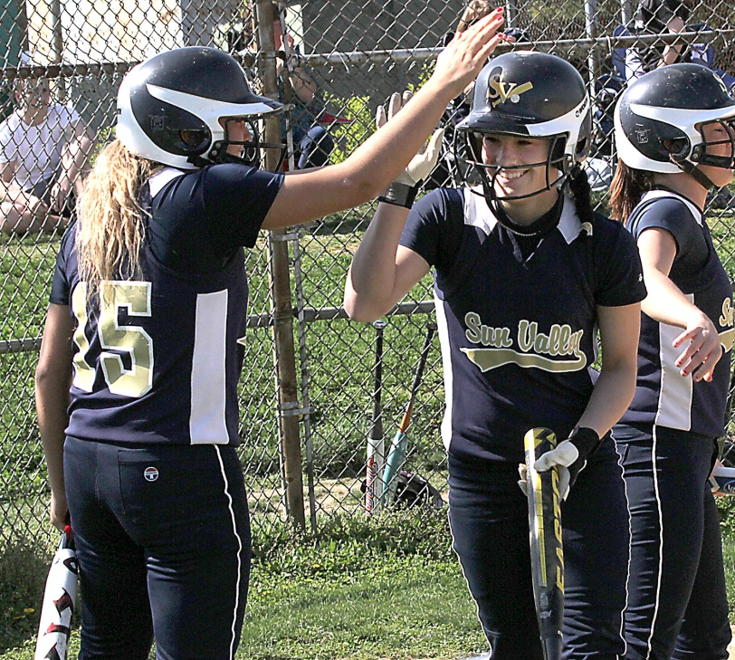 Sun Valley's Amber Michael, right, gets congratulated by Amanda Lewis after hitting an inside the park homer against Oxford Friday. (Times Staff/ROBERT J. GURECKI)