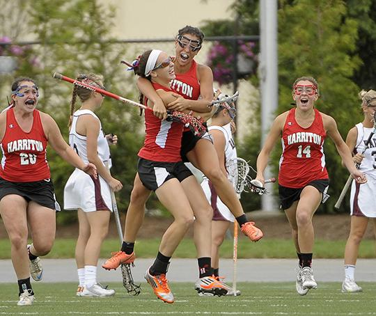 Harriton's Caleigh Foust, on the right in this big hug, shows moderate excitement about her state-title winning overtime goal.  TIMES STAFF/ERIC HARTLINE