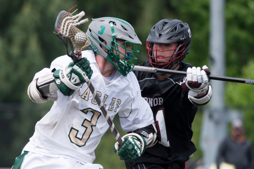 Radnor defenseman Mike Farnish, right, checking Bishop Shanahan's Alex Wagner during the District One quarterfinals May 16, will lead his Radnor team into the second round of the PIAA Tournament against a familiar foe in Conestoga Saturday. (Times Staff/RICK KAUFFMAN)